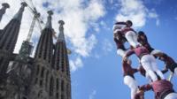 Башня из людей на фоне соборо Святого семейства в Барселоне