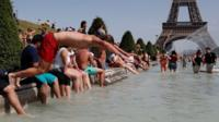 A boy jumps into the water of the Trocadero Fountain in Paris