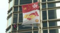 Stunt man Alain Robert ties banner to skyscraper