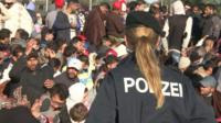 Austrian police officer watches over migrants and refugees