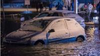 A snow-covered car in flood waters