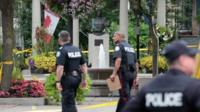 Police are seen near the scene of the shooting in Toronto, Canada, 23 July