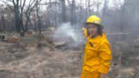 BBC's Sydney Correspondent Shaimaa Khalil stands amid burnt trees and flattened land in Balmoral, Australia.