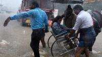 People assist person in a wheelchair through waterlogged streets in Chennai