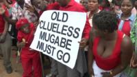 Protesters holding a sign reading 'Old clueless Mugabe must go'