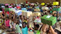 Children holding up presents in boxes