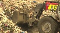 Digger shovelling waste plastic