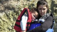 Syrian migrant women hold babies wearing life-jackets before boarding a dinghy to cross the Aegean Sea to the Greek island of Lesbos from the Ayvacik coast in Canakkale on 28 February 2016.