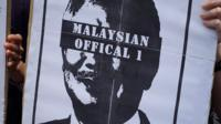 "Protester's sign, with an image of Najib Razak with his eyes blacked out by text reading ""Malaysian Official 1"""