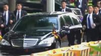 Bodyguards run alongside the car of North Korea leader Kim Jong-un
