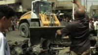 A bulldozer clears the wreckage following a car bomb attack in Sadr City
