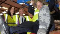 Boris Johnson swinging from a chassis at Wrightbus