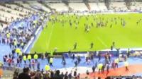 Amateur footage of people streaming across pitch