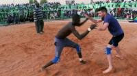 BBC reporter Ben Zand (R) and his opponent (L) in a wrestling match in Khartoum