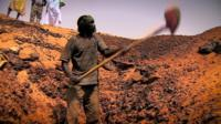 A man digging for gold in the Sahara desert in Mauritania