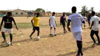 Young Nigerian footballers doing a drill on a training pitch