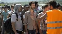 Migrants wait to complete registration in Lesbos