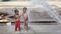 Indian children cool themselves to beat the heat at a construction site at outskirt of Delhi, India