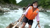 Carmen Roberts rides on a log raft down a river