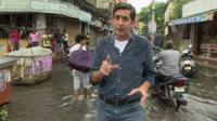 Justin Rowlatt in a flooded street