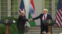 Mr Modi clamps the US president's hands firmly, offering no escape
