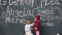 "Children playing in front of board with chalk messages on it saying: ""To Germany, please. Angela Merkel I will not stay here"""