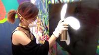 Woman graffitis a Hong Kong flag