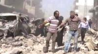 People walk in the rubble in Qamishli