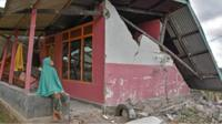 Woman sits outside a damaged house in Sembalun Bumbung village
