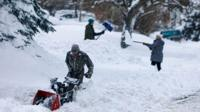People clearing snow in Lakewood, Colorado.