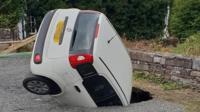 A white Fiat in a sinkhole
