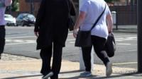 Two women walking on a street