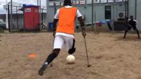 Emmanuel Ibeawuchi on crutches takes a penalty kick