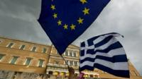 Protesters wave Greek and EU flags