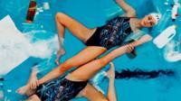 Синхроннное плавание в бассейне с пластиковым мусором.