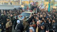 Crowds gather around a vehicle at the funeral of Qasem Soleimani in Baghdad