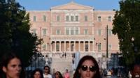 People walk past the Greek parliament in central Athens