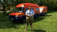 Jared Colclough stands in front of the camper and caravan he's converted to look like lifeboats