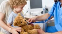A doctor puts a stethoscope on a child's teddy bear
