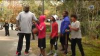 Shaquille O'Neal plays basketball with local children in Florida.