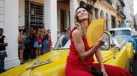 Gisele sitting on a car in Havana