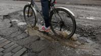 Man cycles through pothole