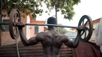 body builder with massive shoulder muscles lifts heavy weight outside