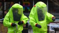 Two emergency service workers in bright green hazmat suits