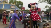 Man wheeling Minnie Mouse on trolley
