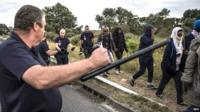 French police officers escort migrants who were waiting alongside a road near the Eurostar train tracks in Coquelles on the outskirts of Calais - 3 August 2015