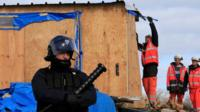 "Workmen destroy a makeshift shelter during the partial dismantlement of the camp for migrants called the ""jungle"", in Calais, northern France, 29 February, 2016."