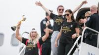 US Women's team exit the plane with their trophy