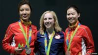 From left: Li Du of China with silver, Virginia Thrasher of the United States with gold, and Siling Yi of China with bronze, pose on the podium following the Women's 10m Air Rifle