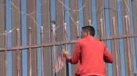 Мигрант лезет на забор на границе США и Мексики